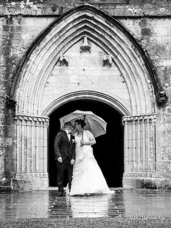 couple de marié s'embrasse en sortie d'église de Ste Mère Eglise en normandie dans la manche