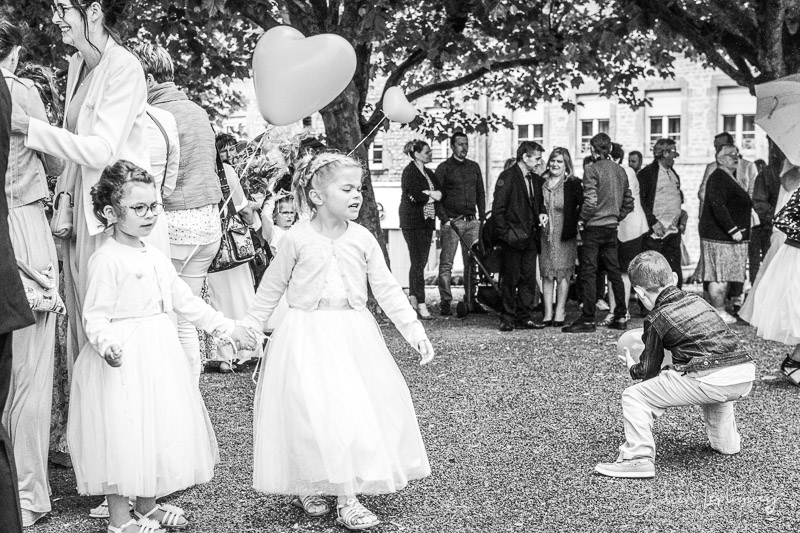 photo sur le vif, les enfants d'honneur jouent avec des ballons coeur au milieu des invités